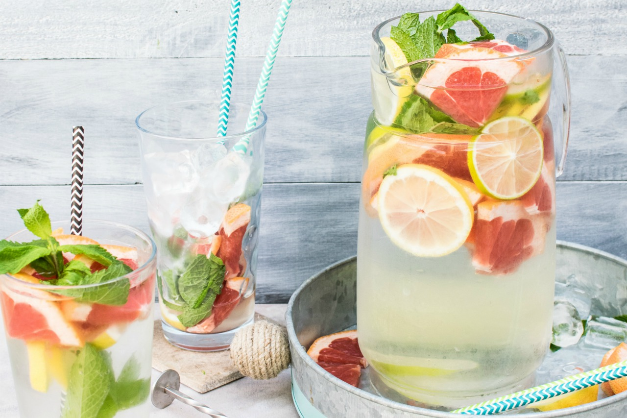 An image of two glasses and a jug filled with citrus and mint infused water