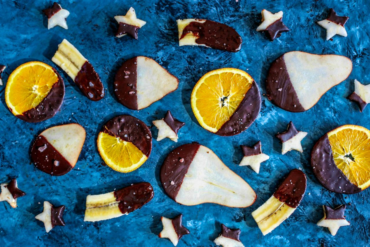 An image of assorted fruits half dipped in chocolate.