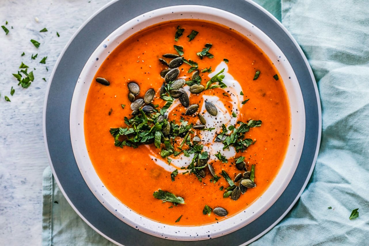 Image of creamy tomato soup topped with coconut yogurt, chopped parsley, and pumpkin seeds.