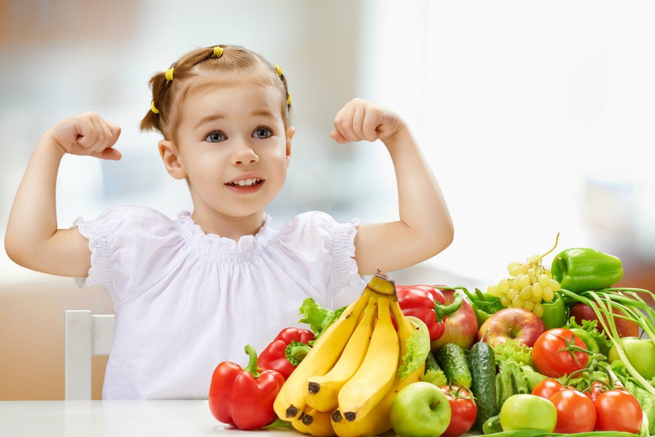 An image of a young girl eating fresh fruit and vegetables