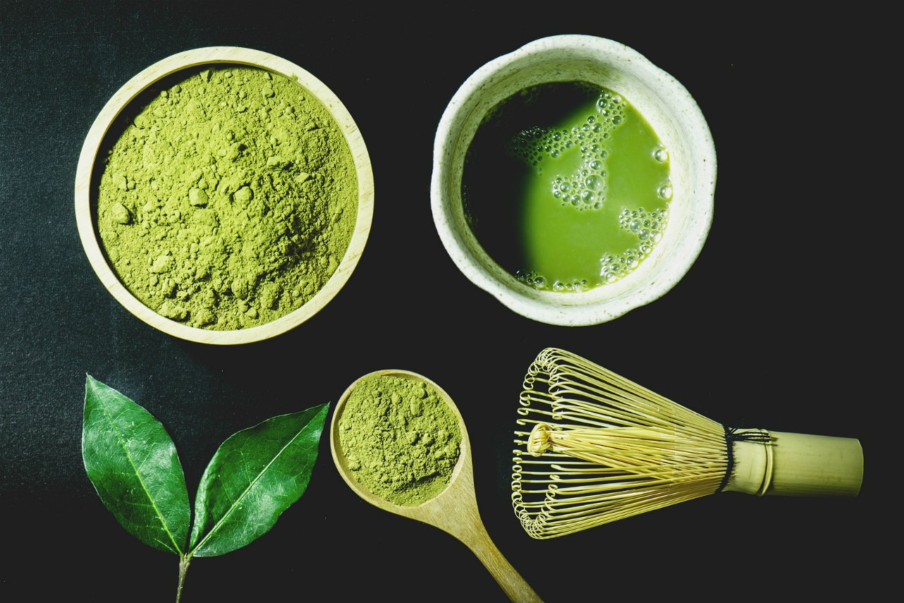 An image of matcha powder, a matcha whisk, and a cup of prepared matcha green tea