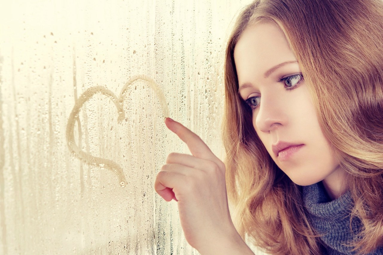An image of a sad woman drawing a heart on the window