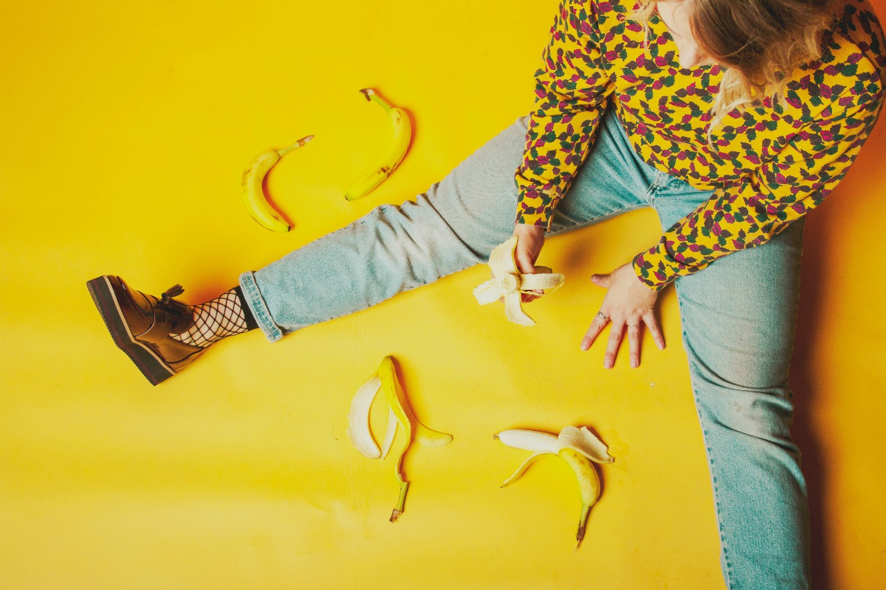 An image of a woman sitting on a yellow floor eating bananas