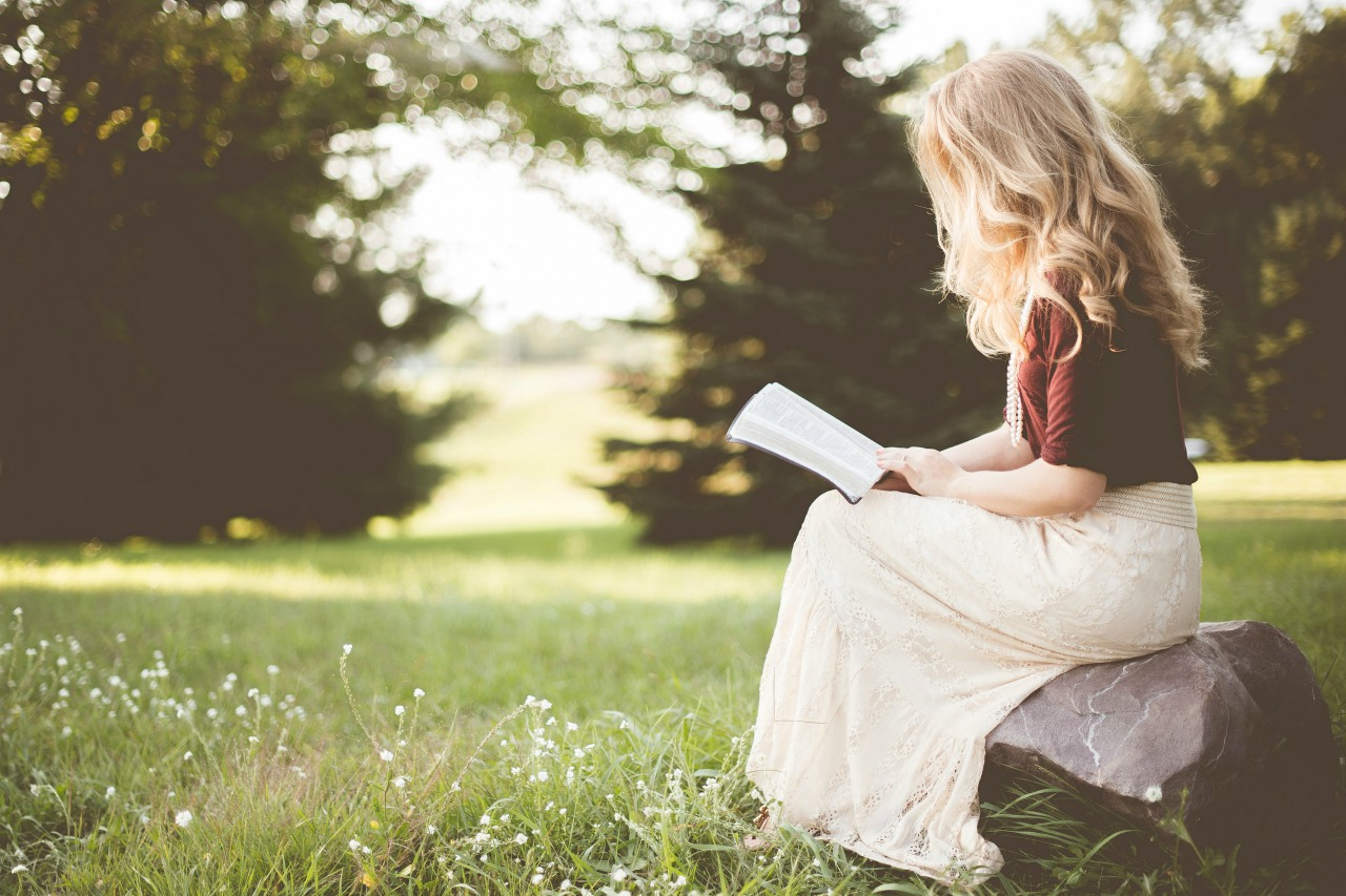 An image of a woman sitting on a rock in a field reading a Bible
