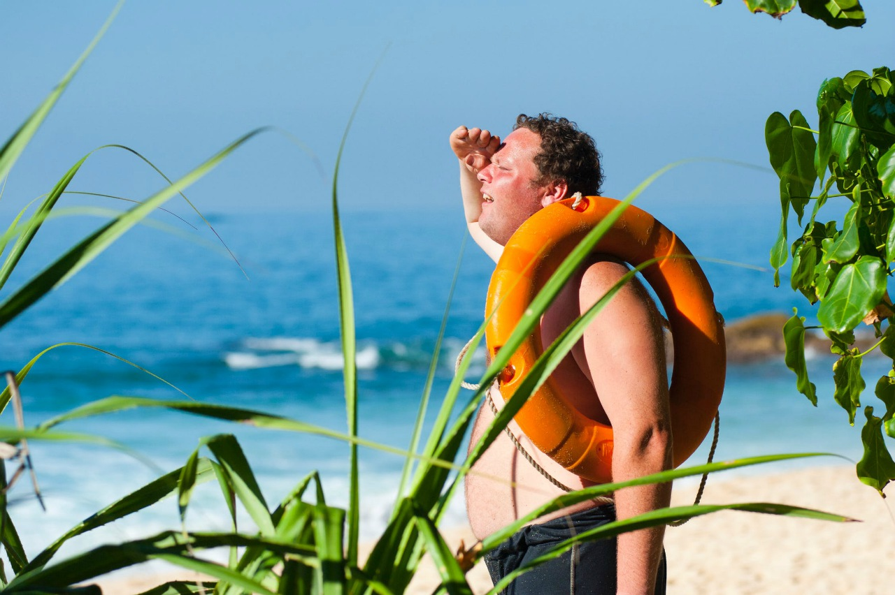 An image of a man on a beach with sunburn