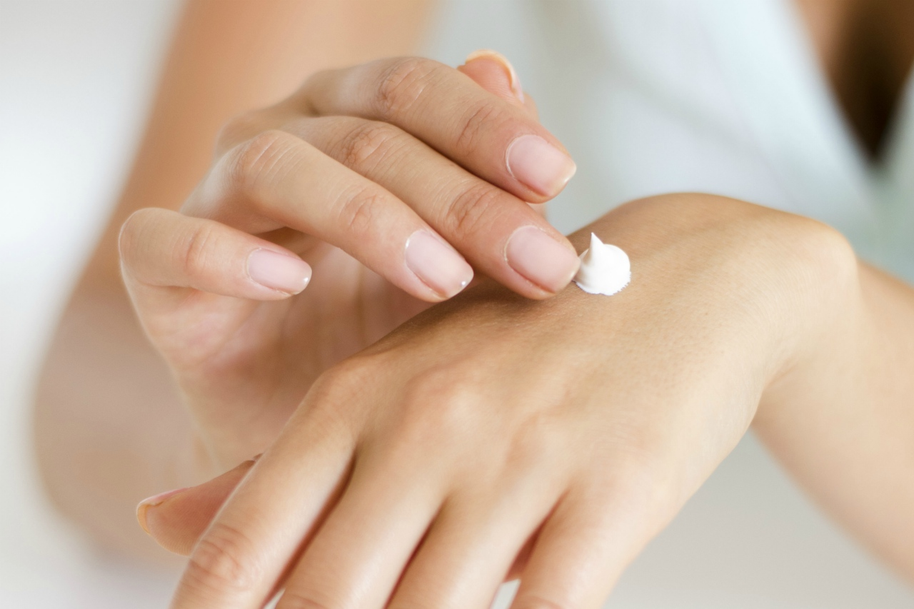 An image of a woman putting moisturizer on her hand