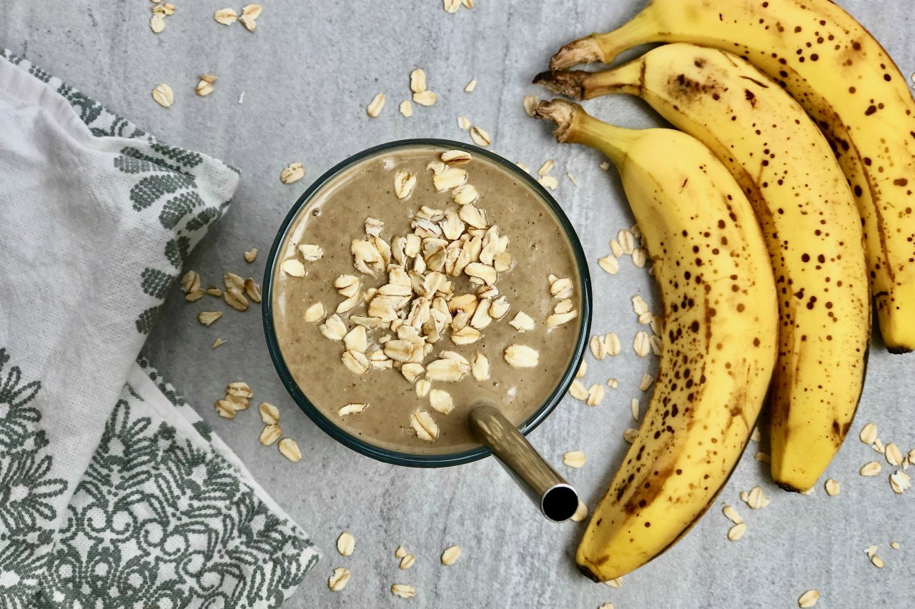 An image of a banana bread protein smoothie in a glass with oats on top.