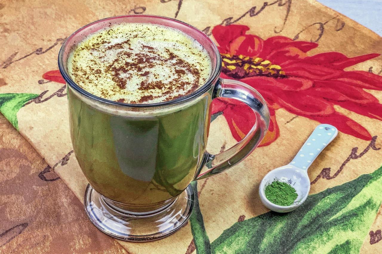 An image of a pumpkin spice matcha latte and a spoon of matcha green tea powder on a floral placemat.