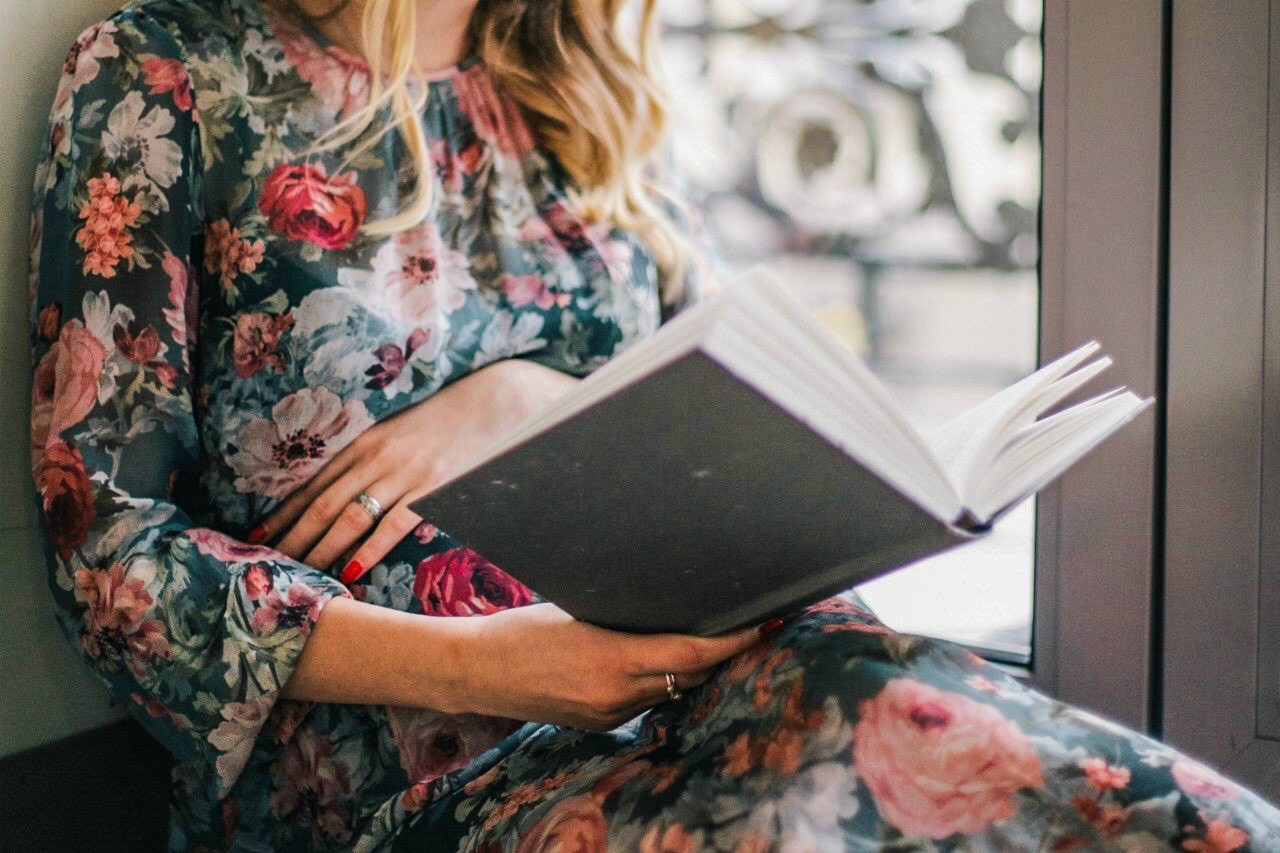 An image of a woman in a floral dress sitting and reading