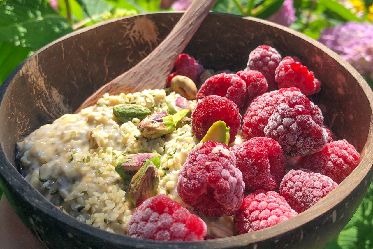 An image of a bowl of lemon raspberry cheesecake overnight oats topped with pistachios and hemp hearts.